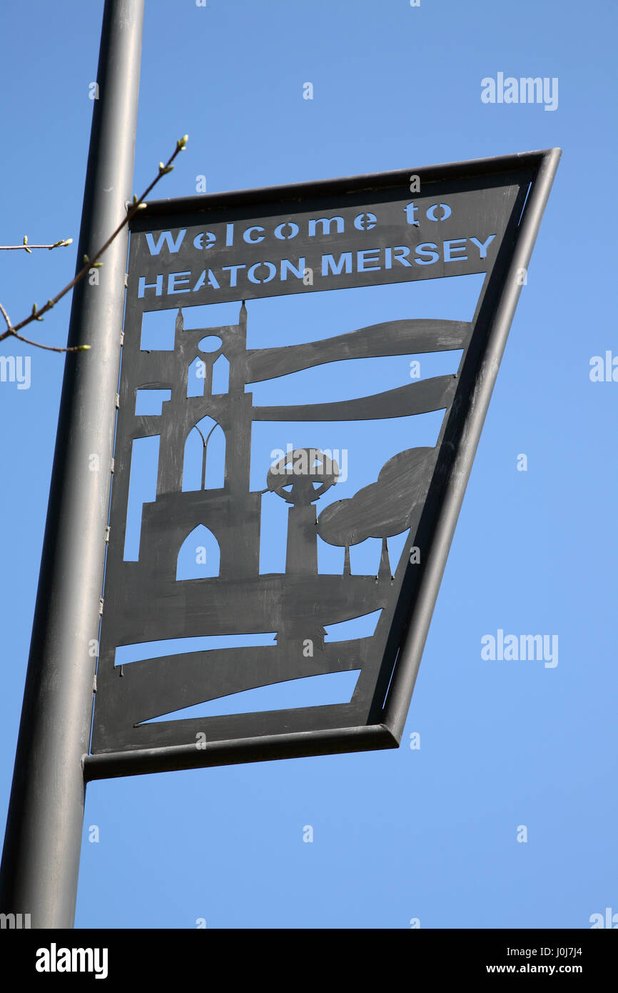 Iron work road sign on lamp post 'Welcome to Heaton Mersey' village between Didsbury and Stockport in Greater - Stock Image