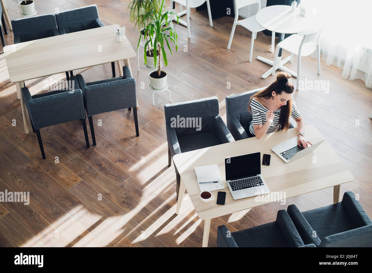 Top view of an adult woman sitting at desk and working on her laptop, her table is perfectly tidy, the sun casts - Stock Image