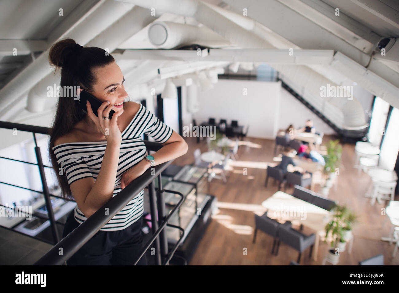 Beautiful smiling young woman leaning on the bar counter and having a phone call - Stock Image