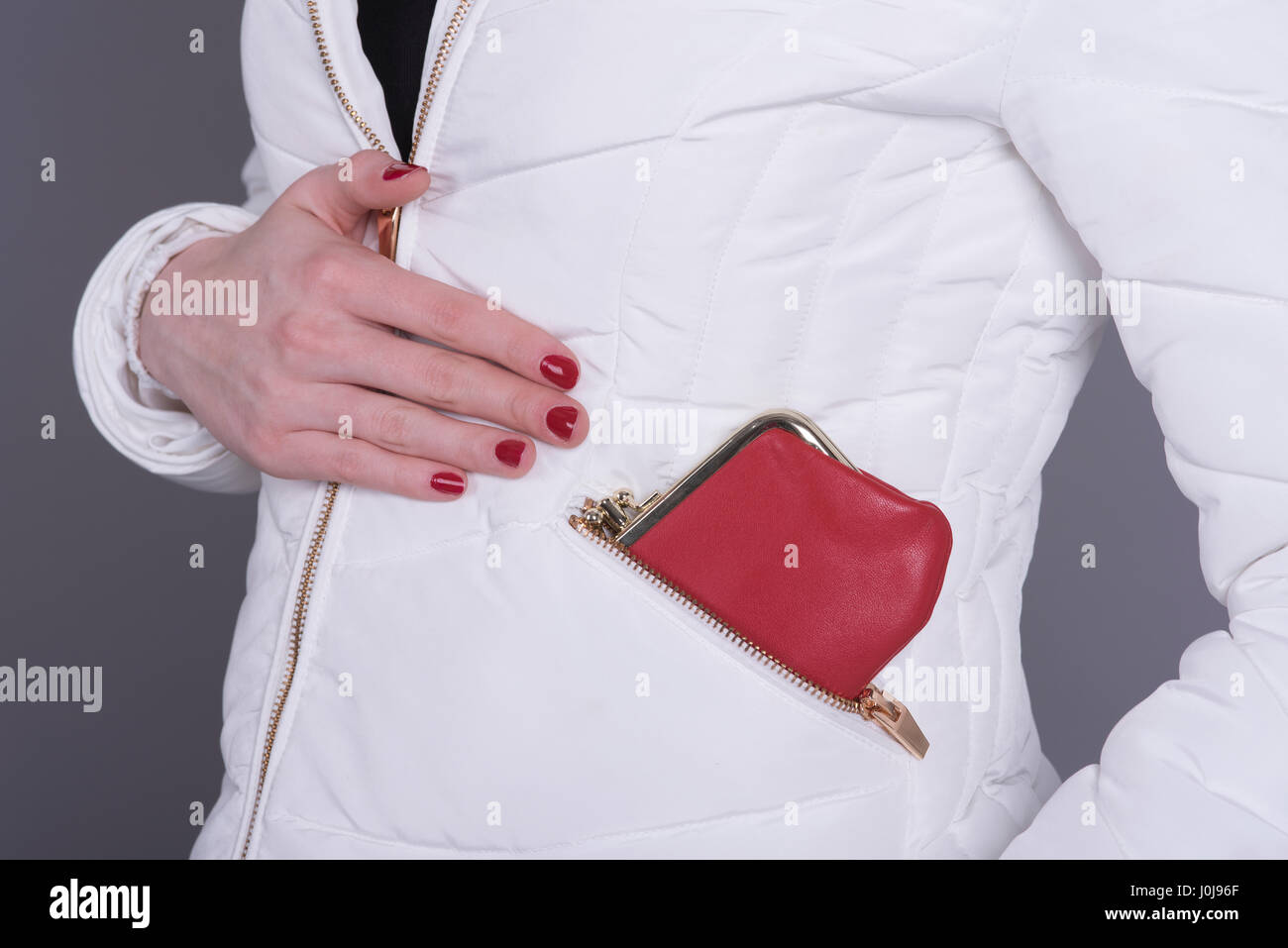 95380d0c51aed Woman wearing a white padded jacket with a red purse in the zipped pocket -  Stock
