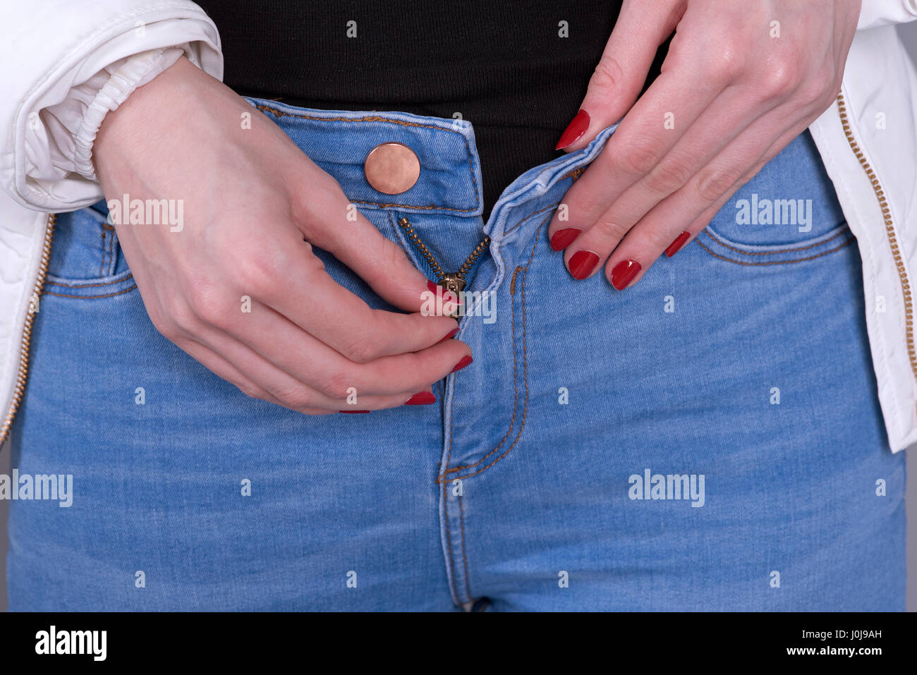 Woman zipping her blue jeans zip - Stock Image