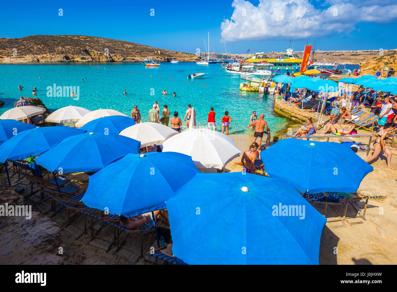 BLUE LAGOON, COMINO, MALTA - October 18, 2016: Tourists crowd to enjoy the clear turquoise water under umbrellas Stock Photo