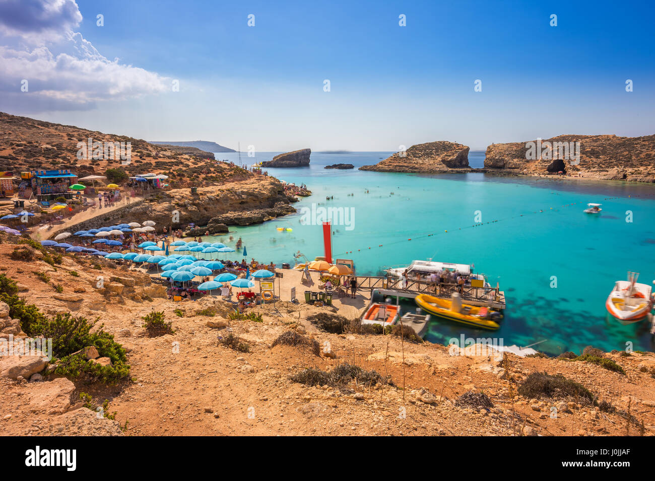 Comino, Malta - Tourists crowd at Blue Lagoon to enjoy the clear turquoise water on a sunny summer day with clear - Stock Image