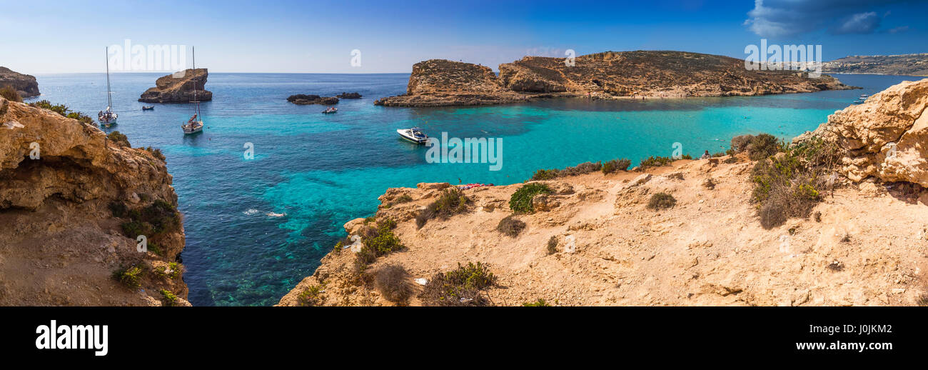 Comino, Malta - The beautiful Blue Lagoon with turquoise clear sea water, yachts and snorkeling tourists on a sunny - Stock Image