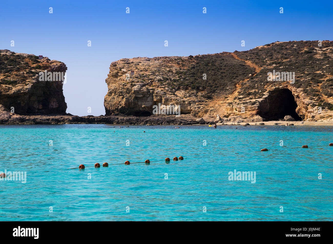 Comino, Malta - Beautiful azure sea water at the famous Blue Lagoon on the island of Comino with clear blue sky - Stock Image