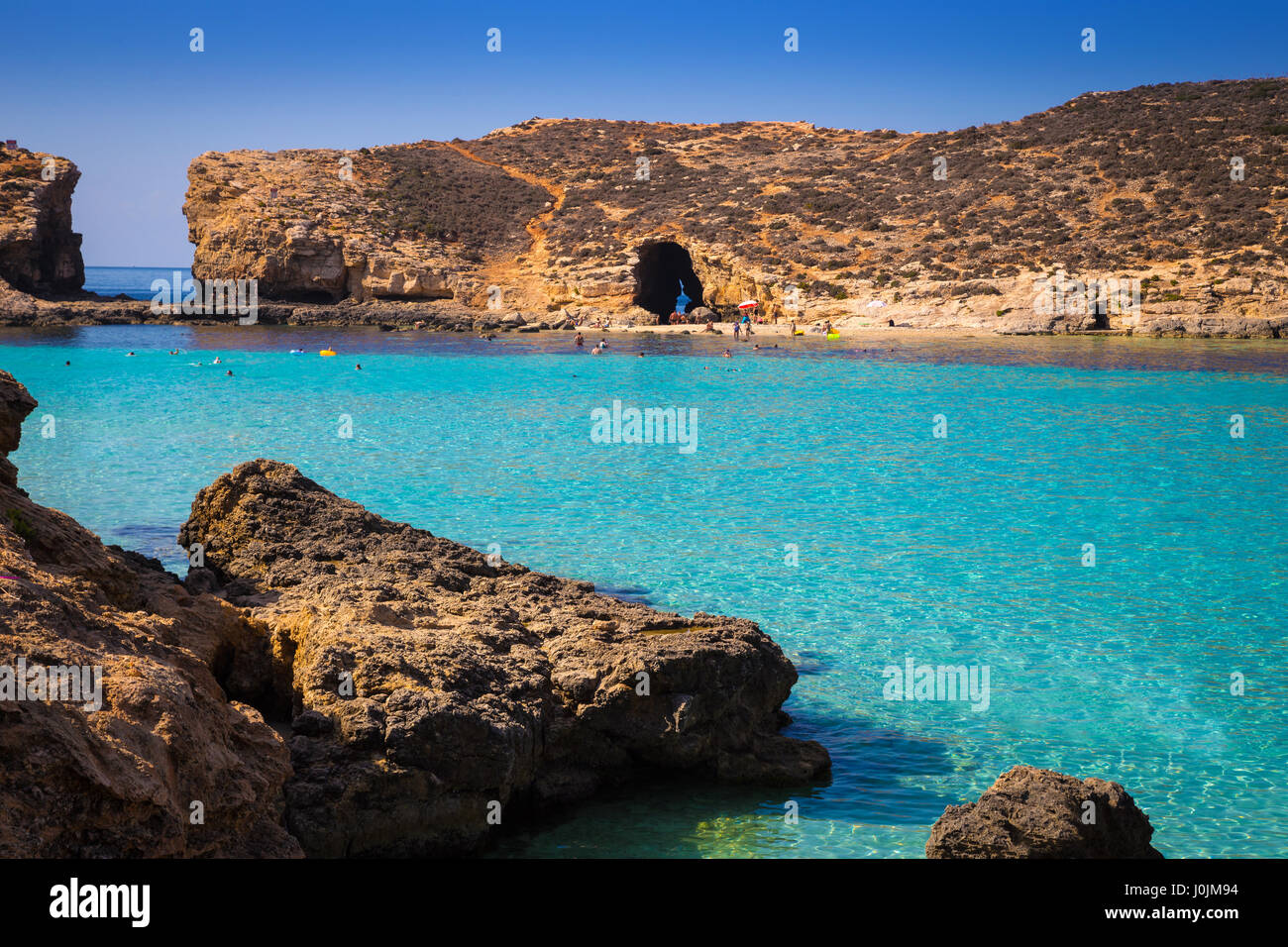 Comino, Malta - Beautiful azure sea water at the famous Bluw Lagoon of Comino with snorkeling tourists enjoying - Stock Image