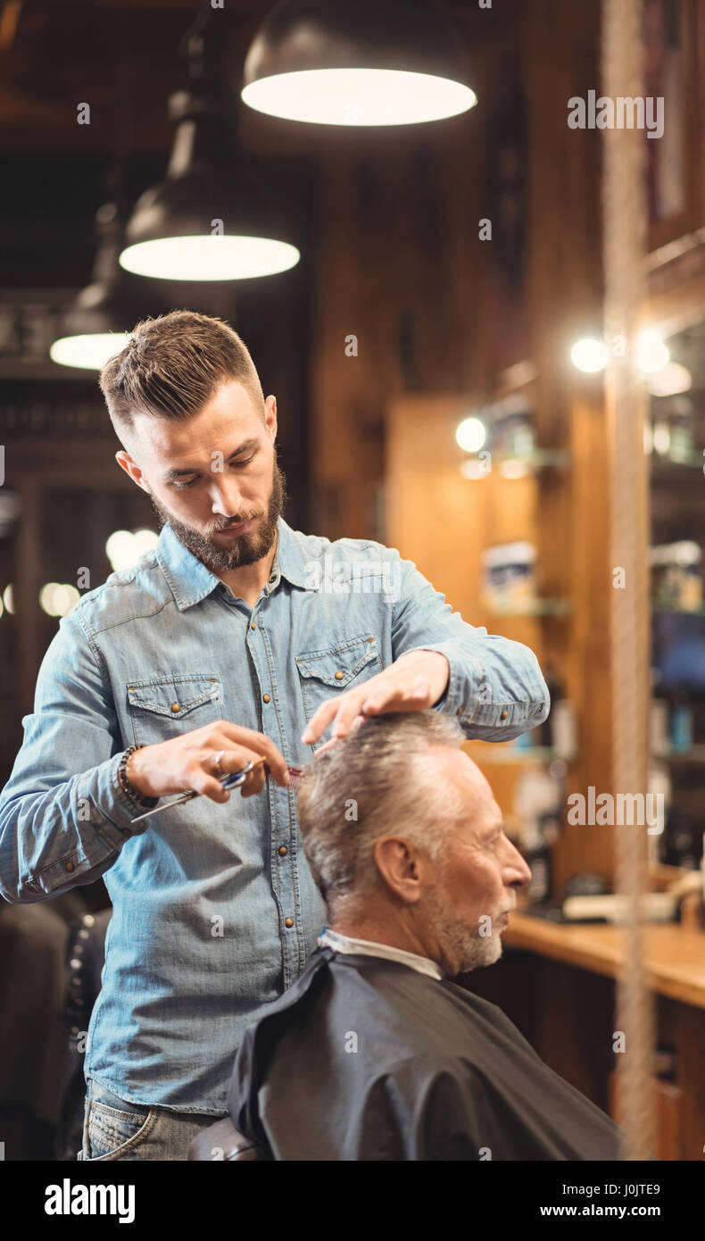 Young barber enjoying working process in the barbershop - Stock Image