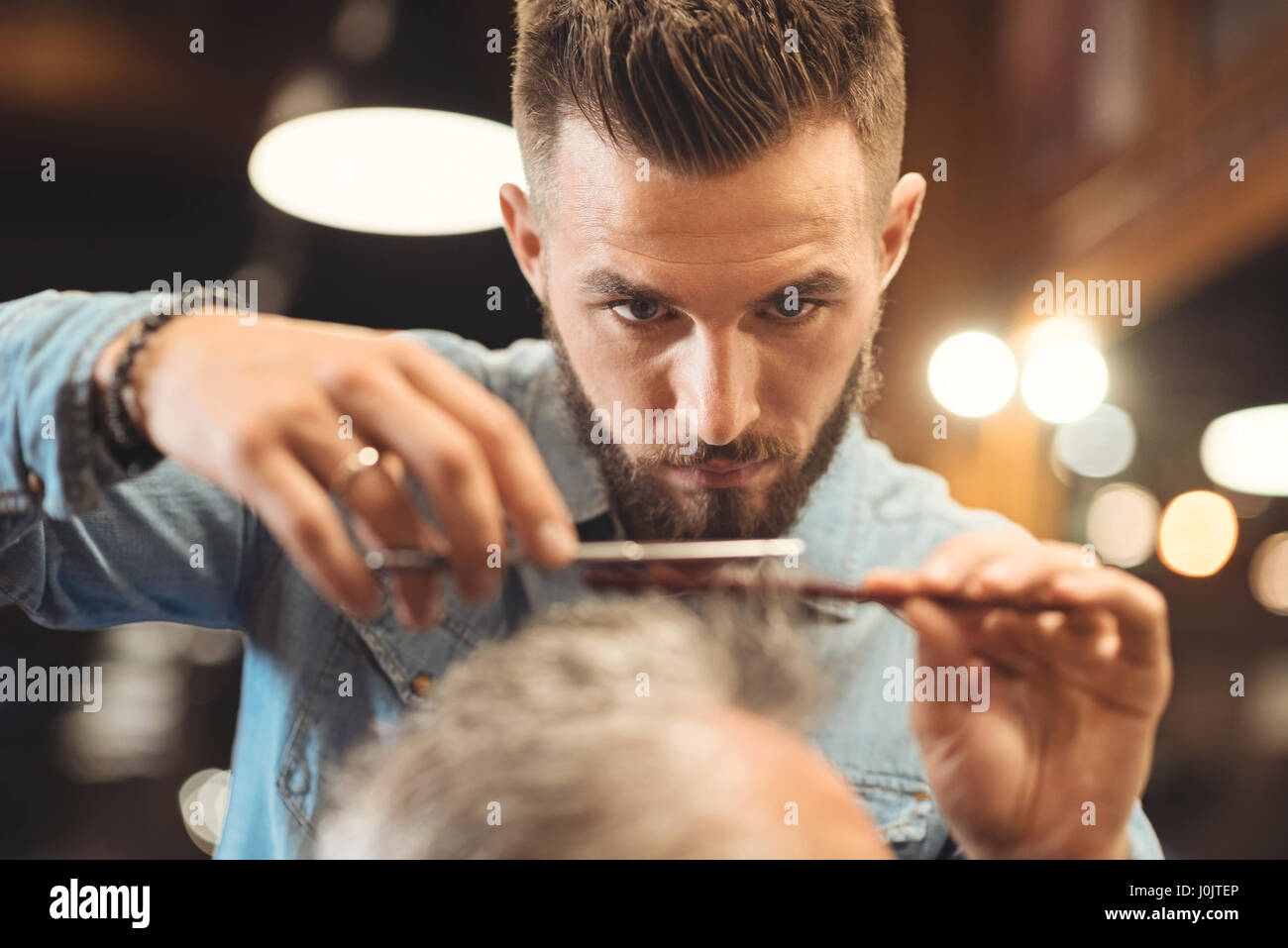 Attentive young barber working in the barbershop - Stock Image