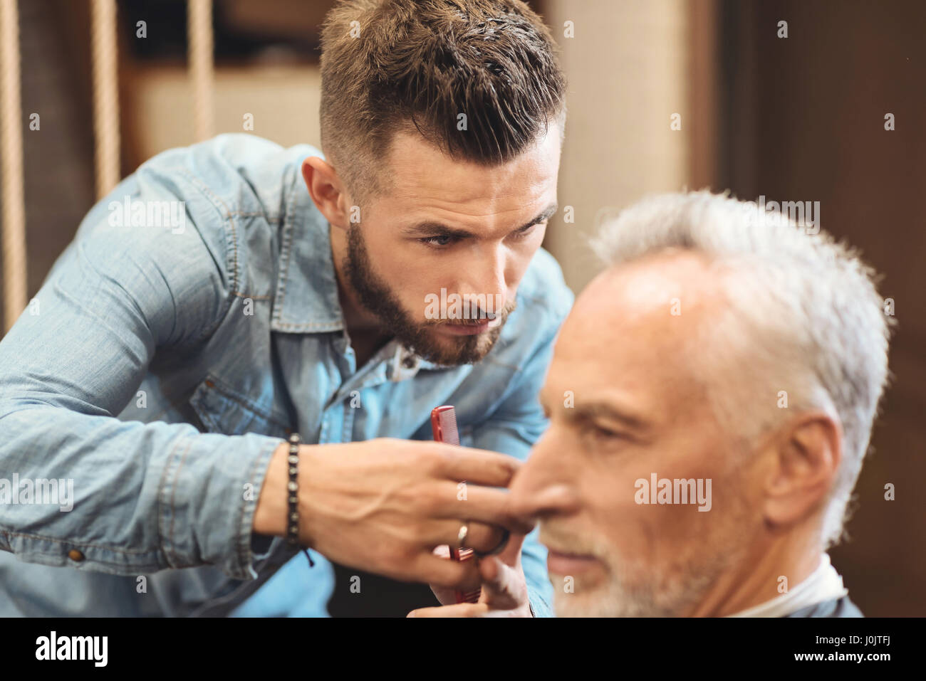 Proficient hairdresser designing haircut in the barbershop - Stock Image