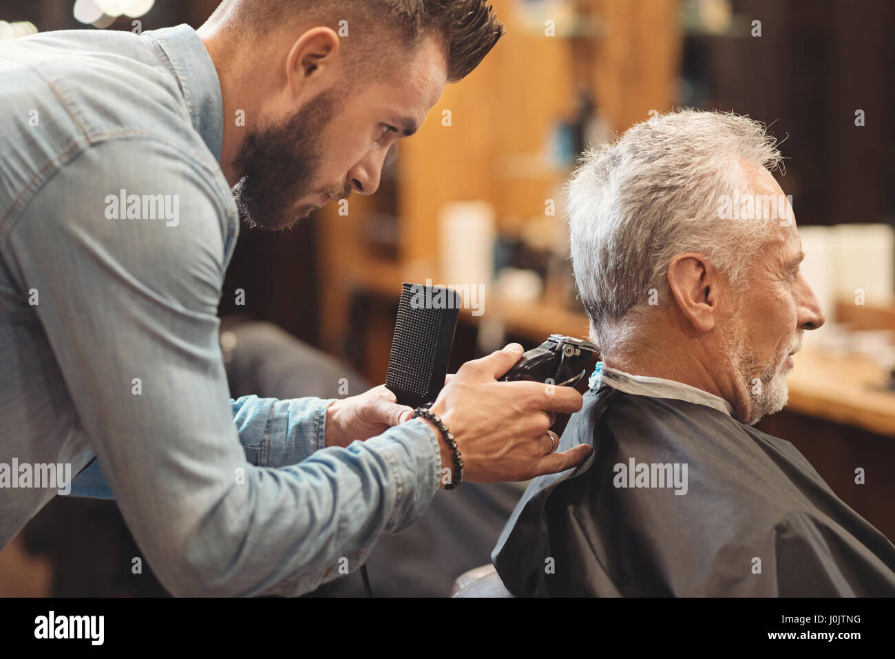 Handsome barber designing haircut of the aging man in barbershop - Stock Image