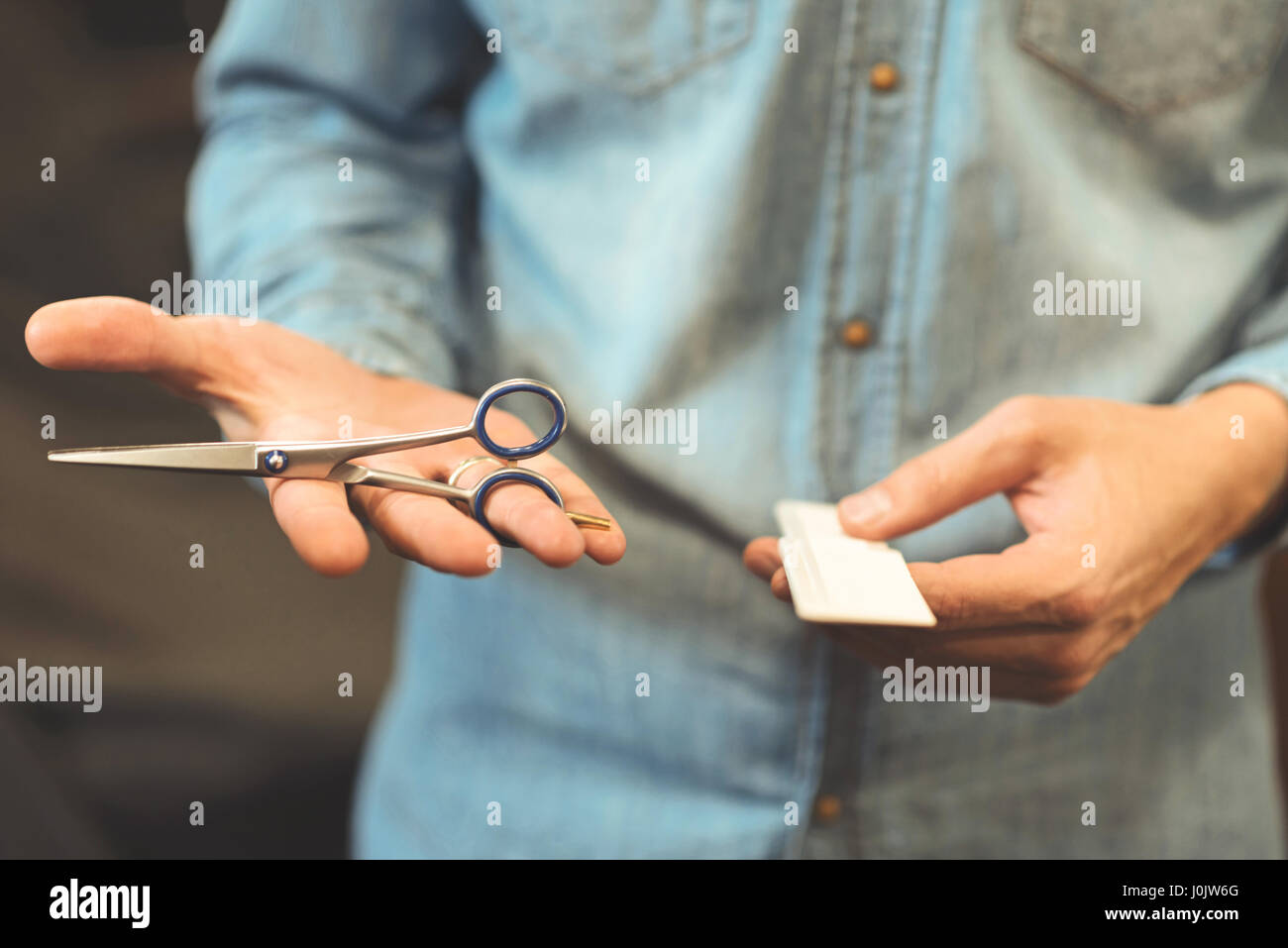 Young master holding comb and scissors in the salon - Stock Image