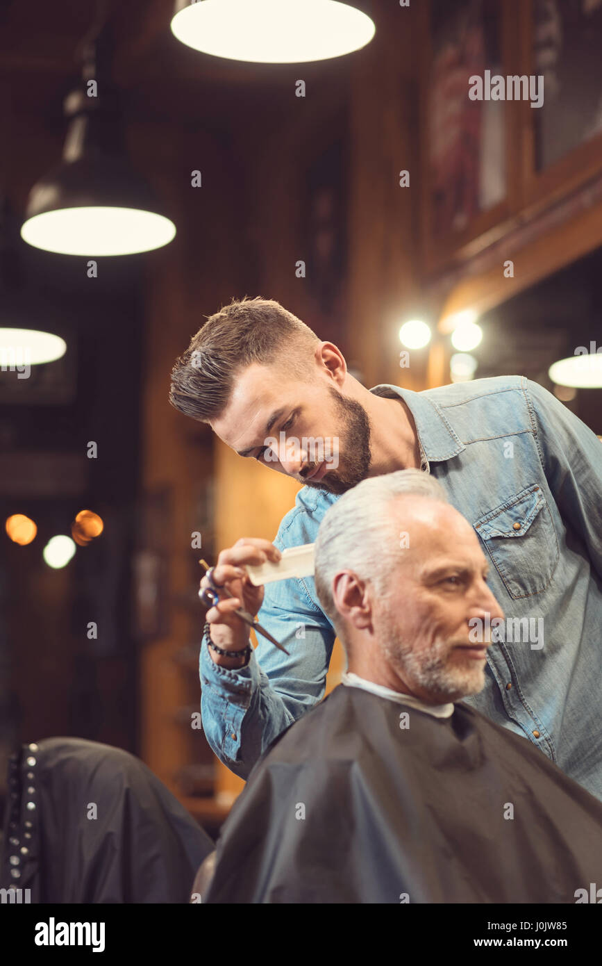 Brutal hairdresser combing haircut of the client in the salon - Stock Image