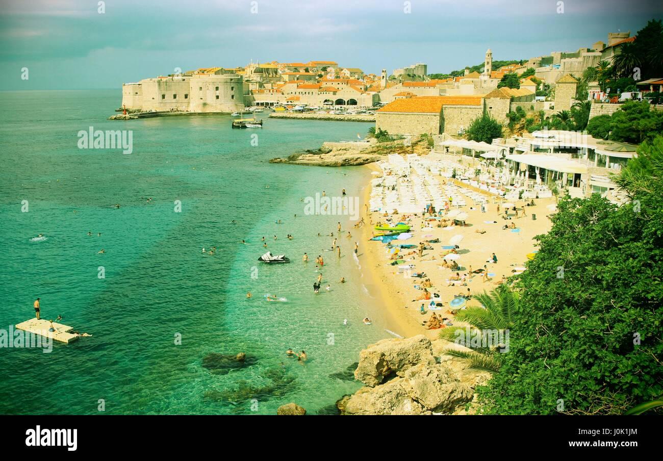 Tourists on sandy beach Banje near Dubrovnik in Croatia, warm colors - Stock Image