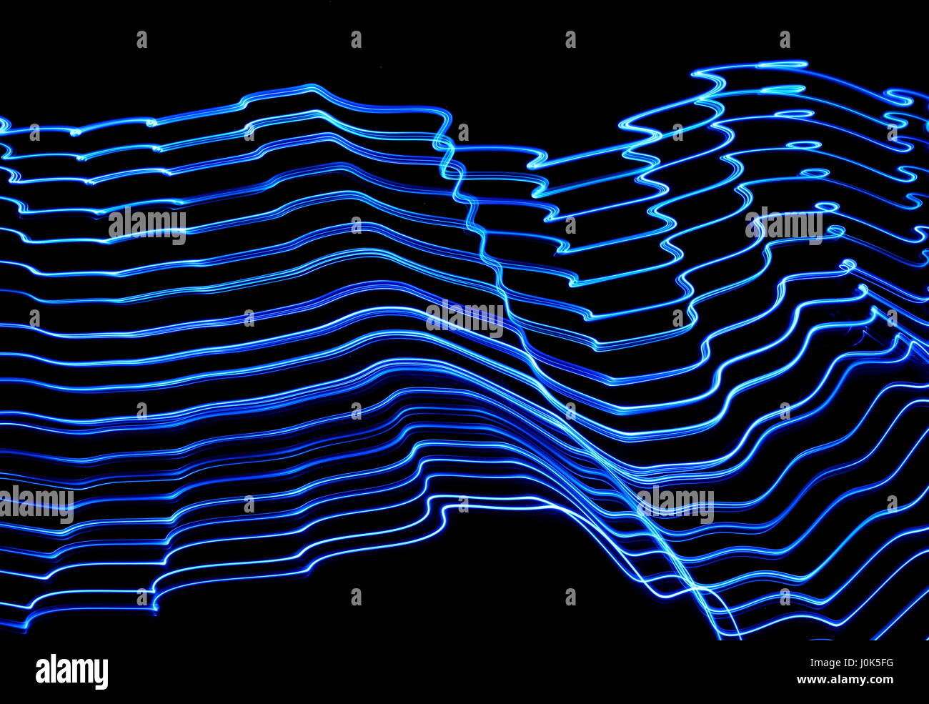 Long exposure photograph of neon electric blue colour in an abstract pattern against a black background. Light painting - Stock Image