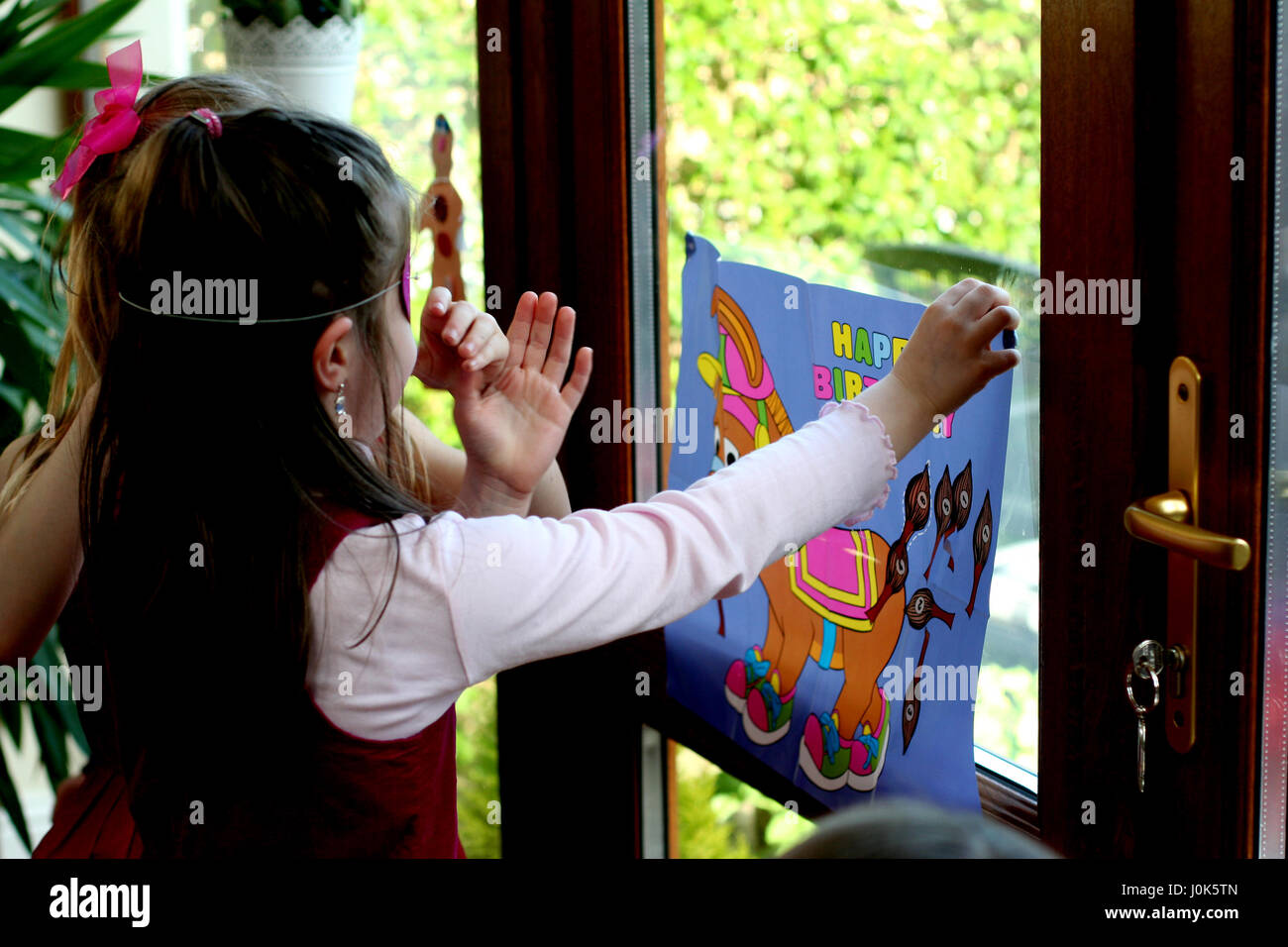 Children blind folded playing pin the tail on the Donkey at a birthday party games concept, childhood fun, joy, Stock Photo