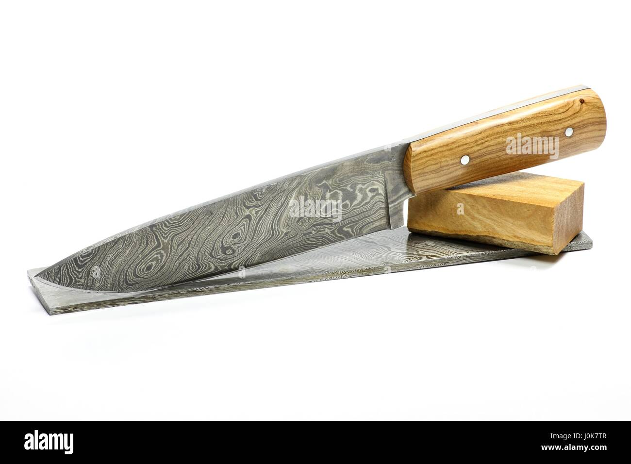 handmade damascus kitchen knife with raw materials isolated on white background Stock Photo