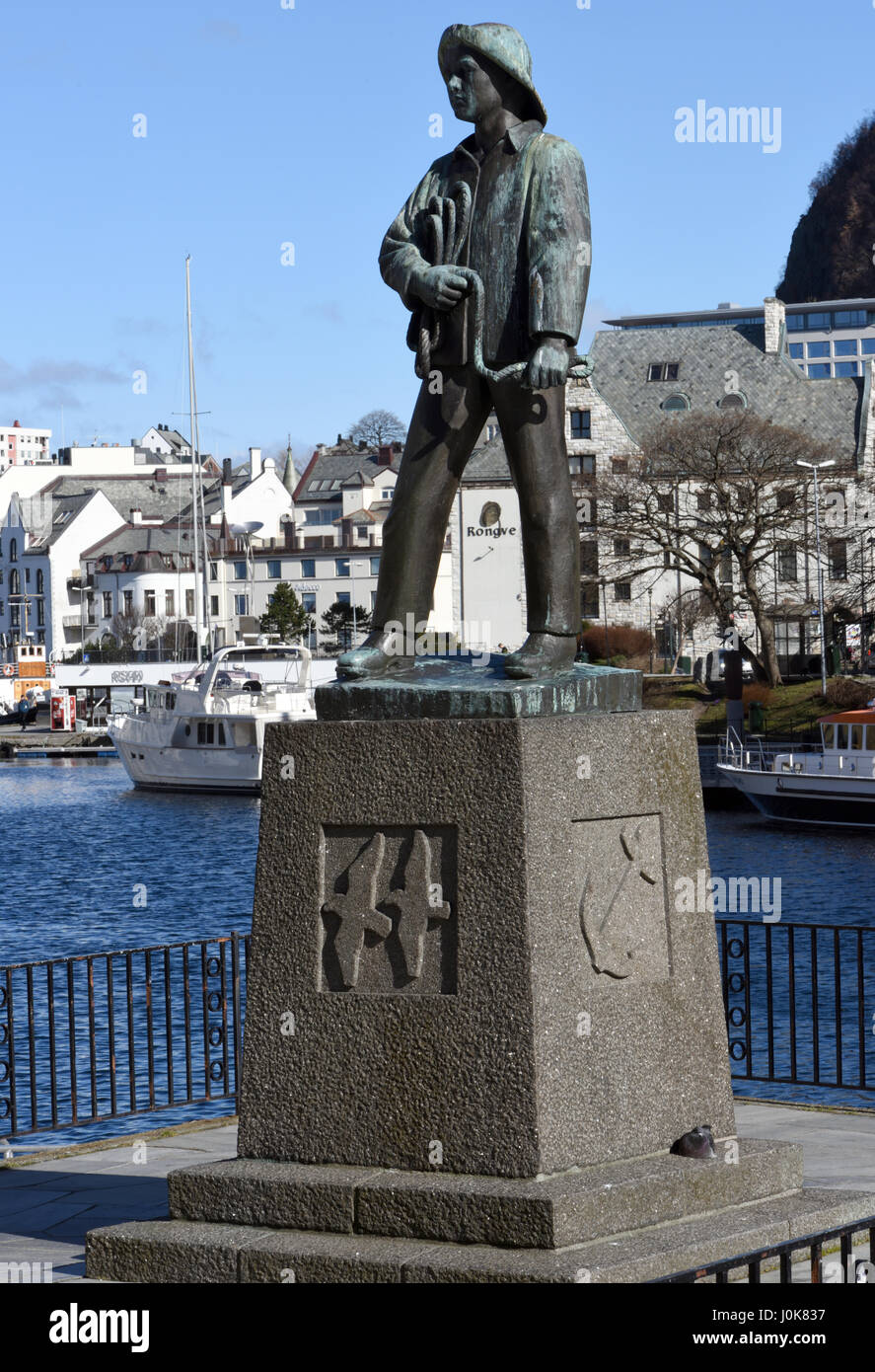 A statue on the waterfront of the harbour at  Alesund. The statue represents a young fisherman: Skårungen, - Stock Image