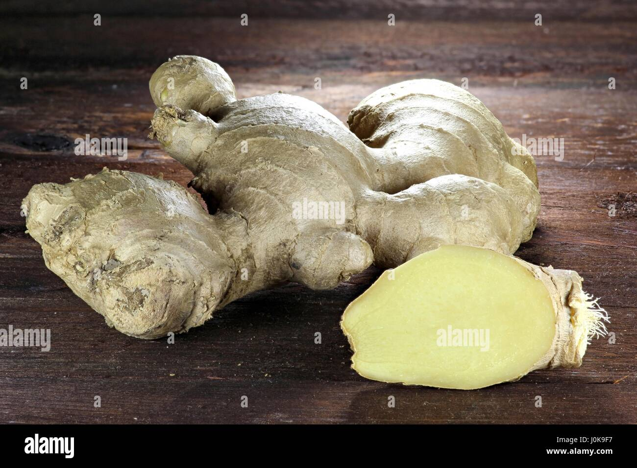 ginger rhizome on wooden background - Stock Image