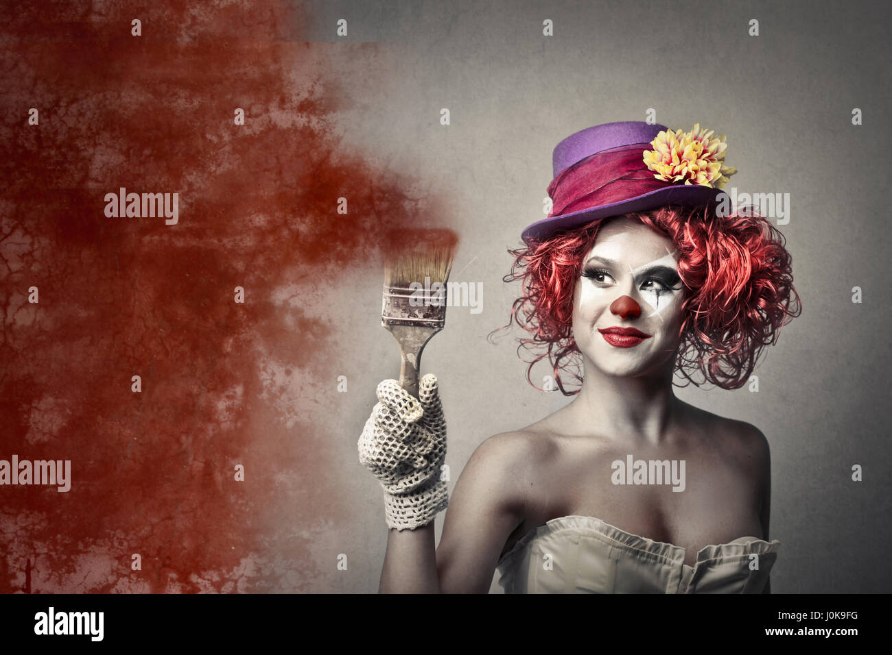 Clown woman with paint brush - Stock Image
