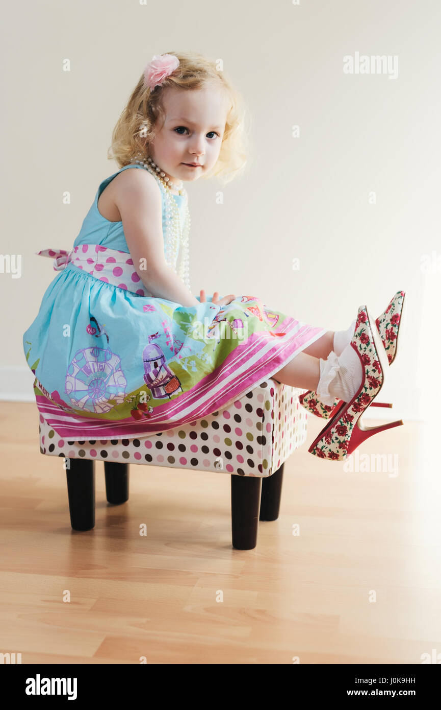 Portrait of a Blond Girl Wearing Adult Size High Heels - Stock Image