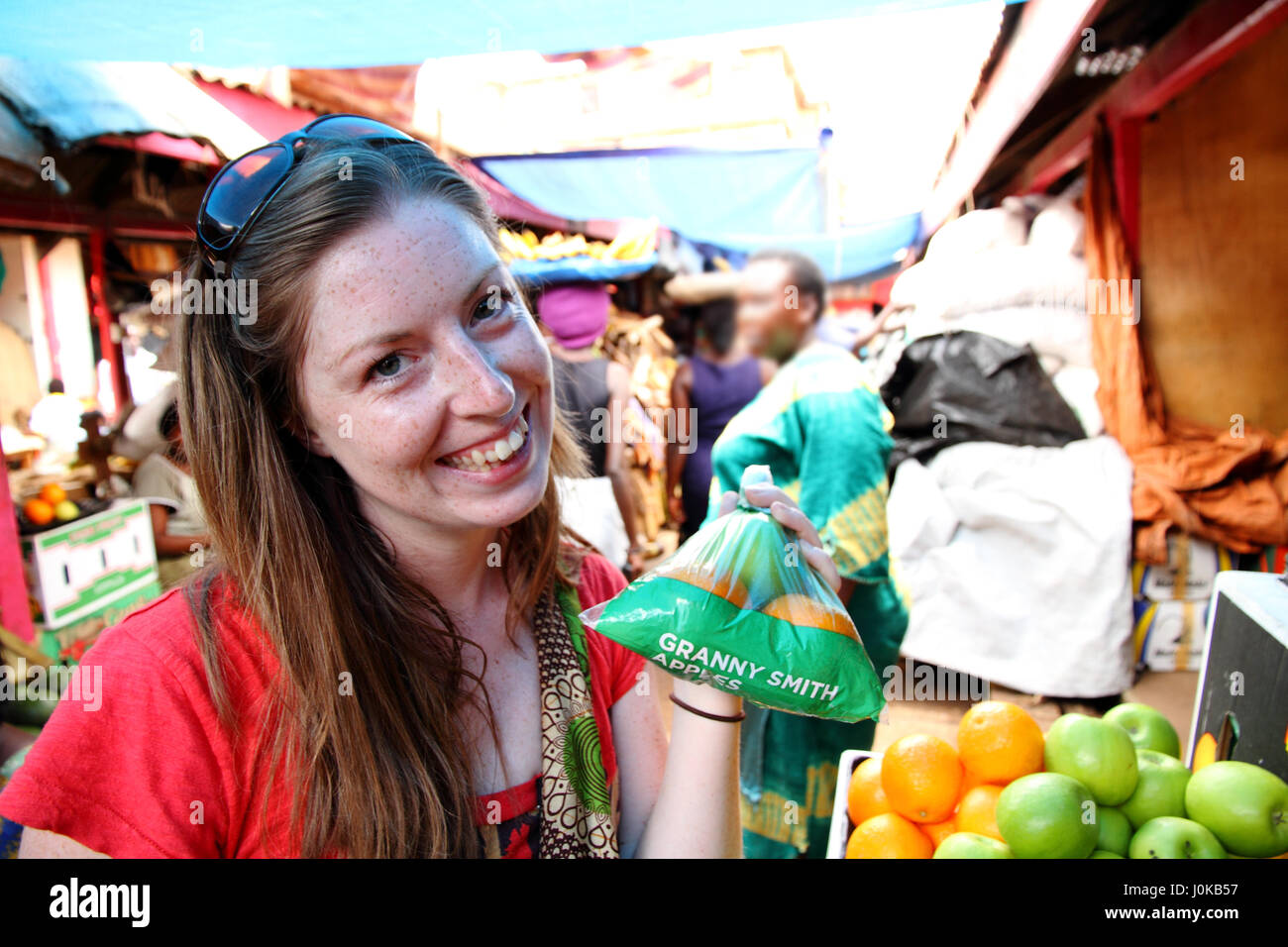 A young freckled Caucasian woman smiles with a bag of apples and oranges she bought in the market - Stock Image
