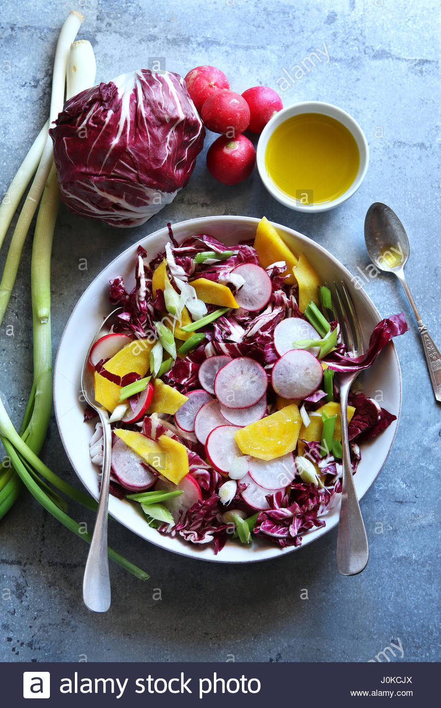 Radicchio salad with radish,spring onion and yellow beetroot on a plate.Top view - Stock Image