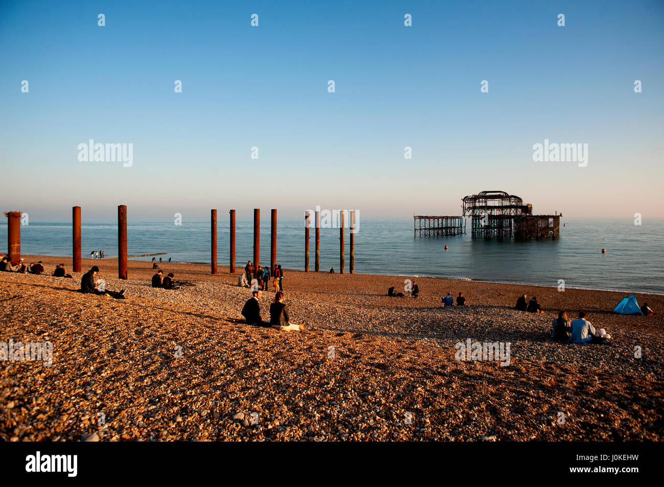 People sit on the pebble beach at Brighton's West Pier a famous landmark on the south coast of England, now a burnt - Stock Image