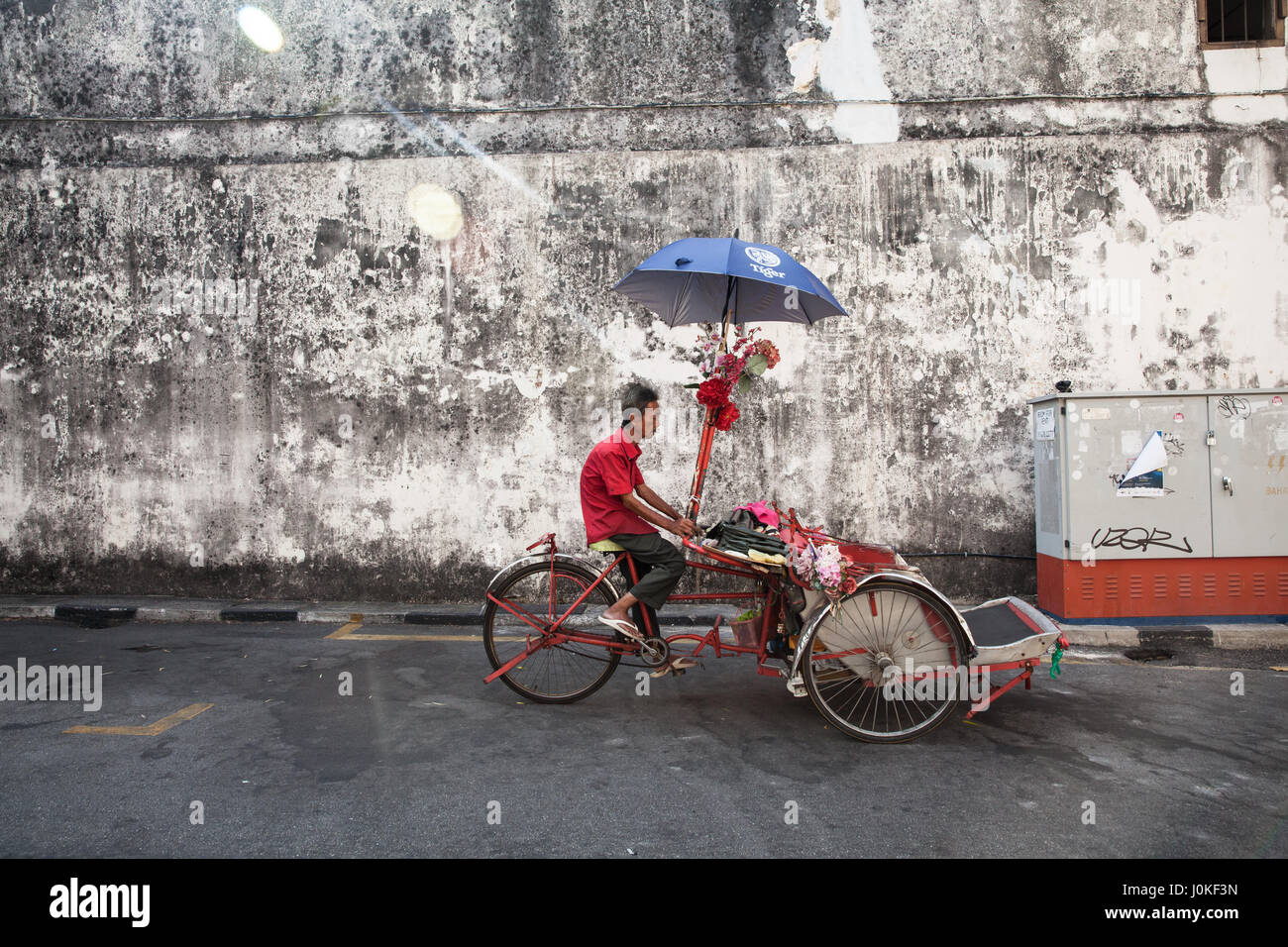 George Town,  Malaysia - March 21, 2016: Cycle rickshaw is riding down the street on March 21, 2016 in George Town, Stock Photo