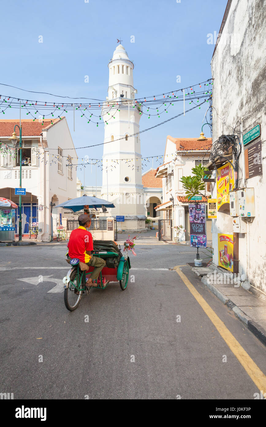 George Town,  Malaysia - March 21, 2016: Cycle rickshaw is riding down the street in front of the Lebuh Aceh Mosque. Stock Photo