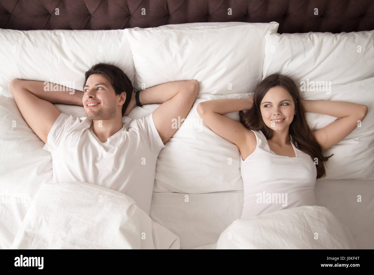 Happy couple lying in bed after wakeup in the morning - Stock Image