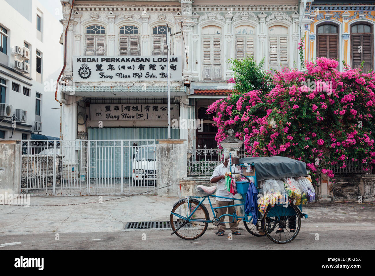 George Town,  Malaysia - March 22, 2016: Vendor sells snacks from the tricycle in UNESCO Heritage buffer zone in Stock Photo