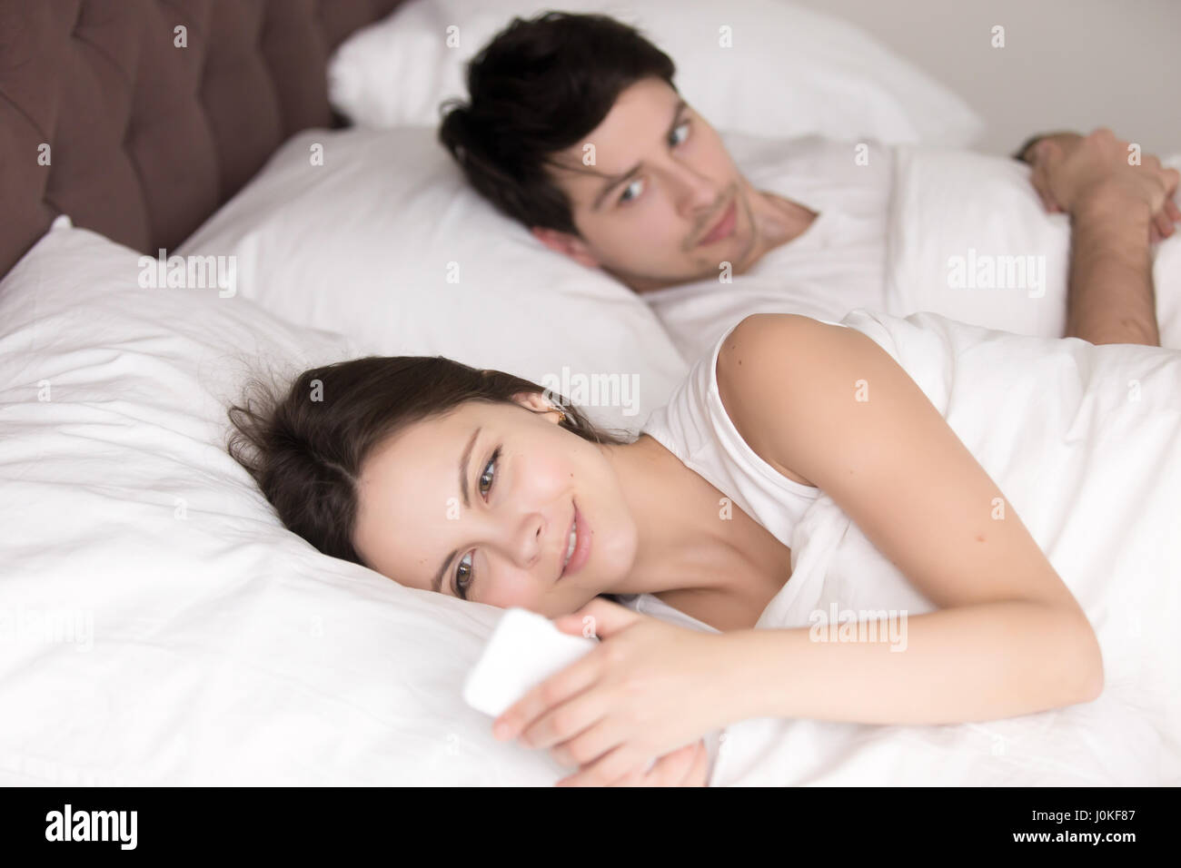 Suspicious guy looking at cheating girlfriend hiding something o - Stock Image