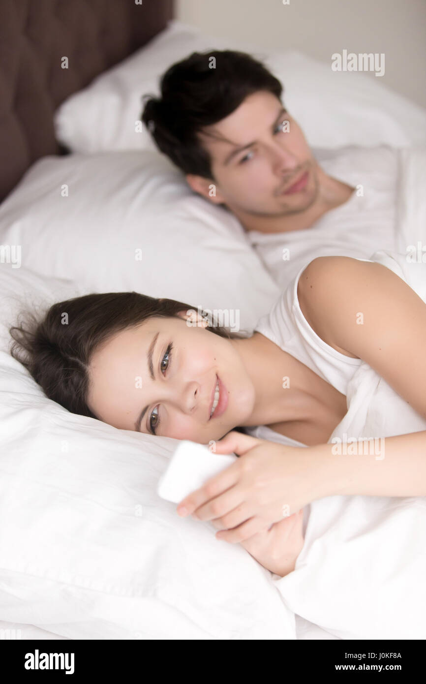 Worried man suspecting his girlfriend cheating using cellphone i - Stock Image