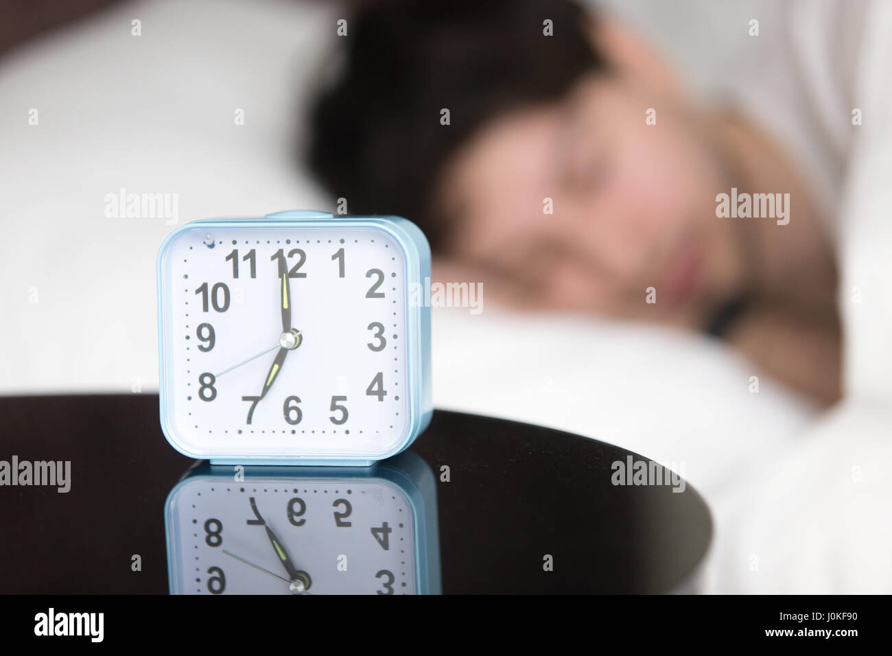 Young man sleeping in bed at home near alarm clock - Stock Image