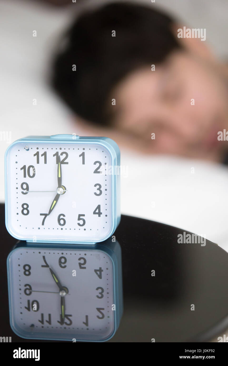 Alarm clock on table in front of sleeping man, vertical - Stock Image