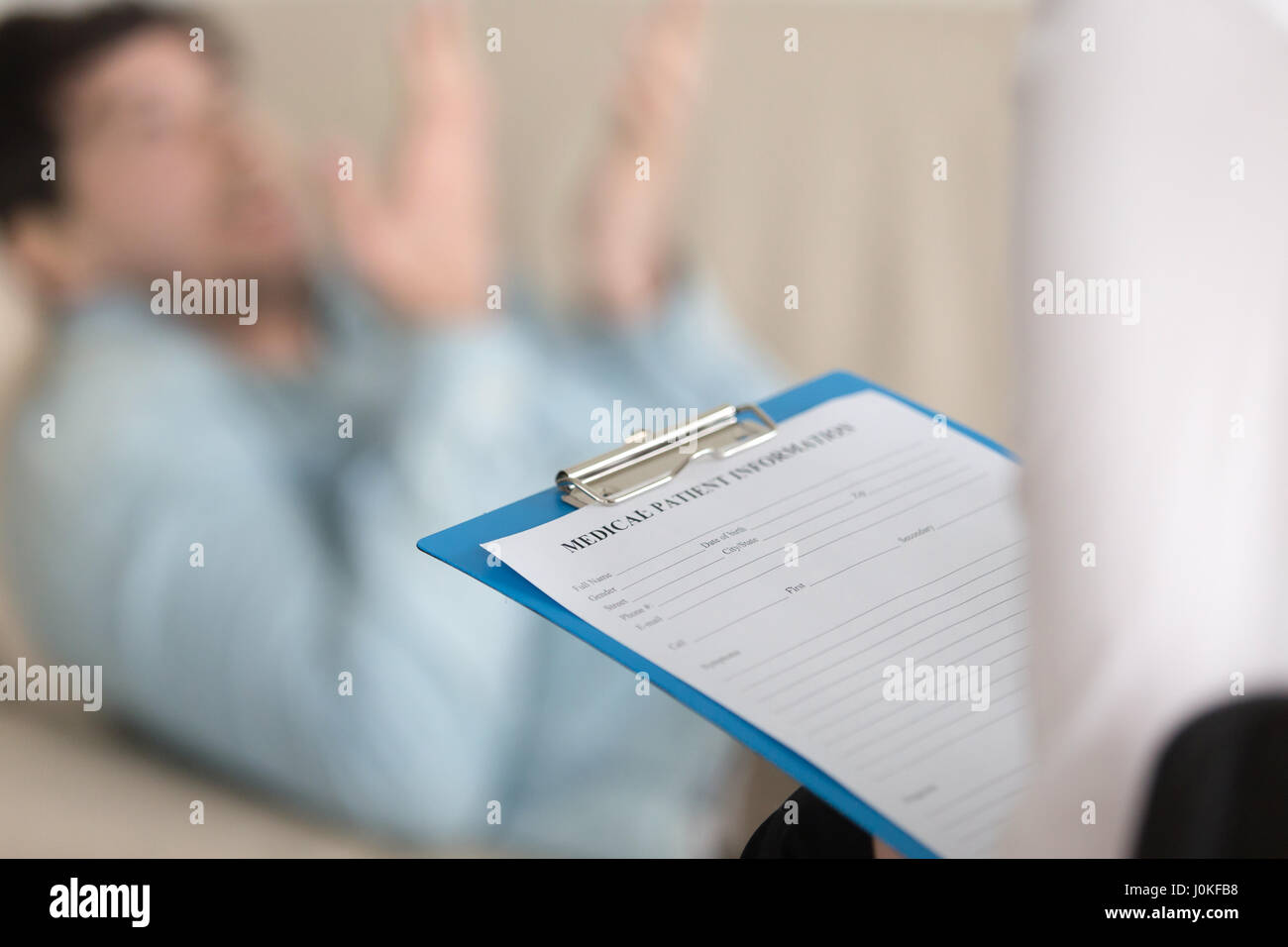 Psychologists office, female practitioner holding clipboard with - Stock Image