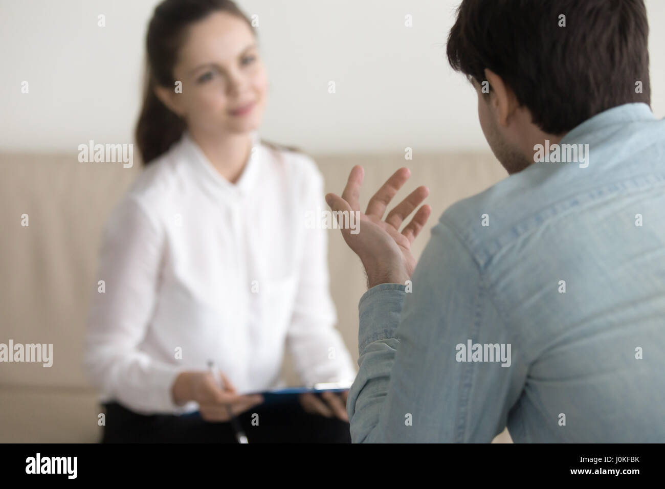 Female psychologist consulting male patient, job interview, busi - Stock Image