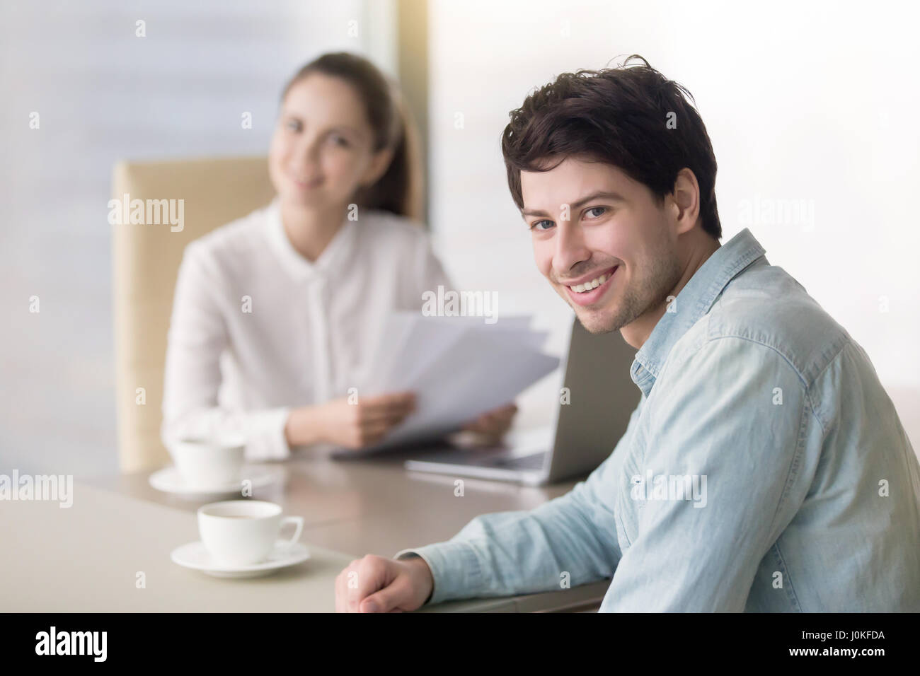 Happy young man satisfied with successful interview with female  - Stock Image