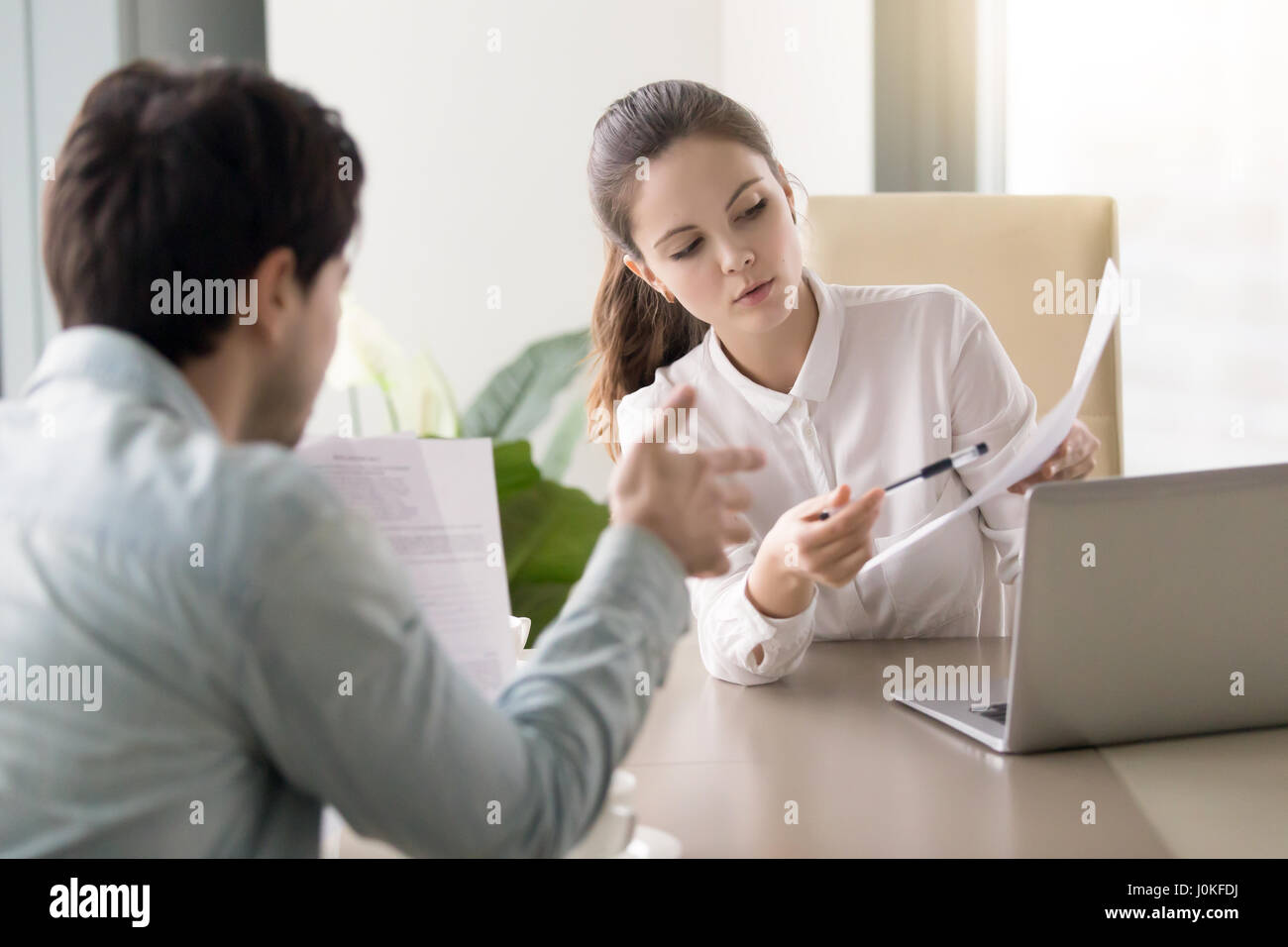 Conversation between businesswoman and businessman about documen - Stock Image