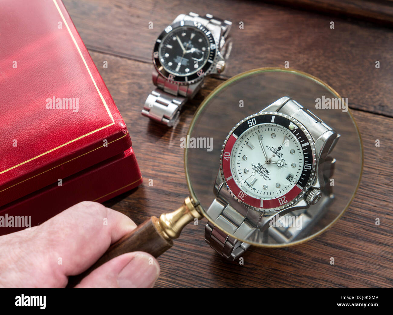 ROLEX WATCHES Magnifying glass and fake replica copy counterfeit men's Rolex watches on old wooden desk top - Stock Image