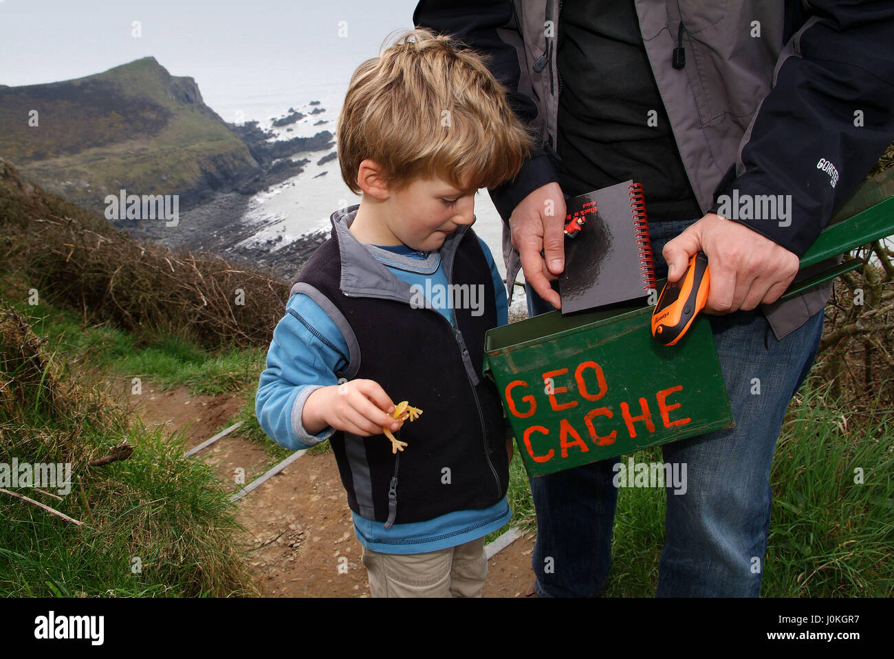 GEOCACHING.  Robert and Linus (5) Uhlig discover and open a Geo Cache box at Hawker's Hut on the coast path - Stock Image