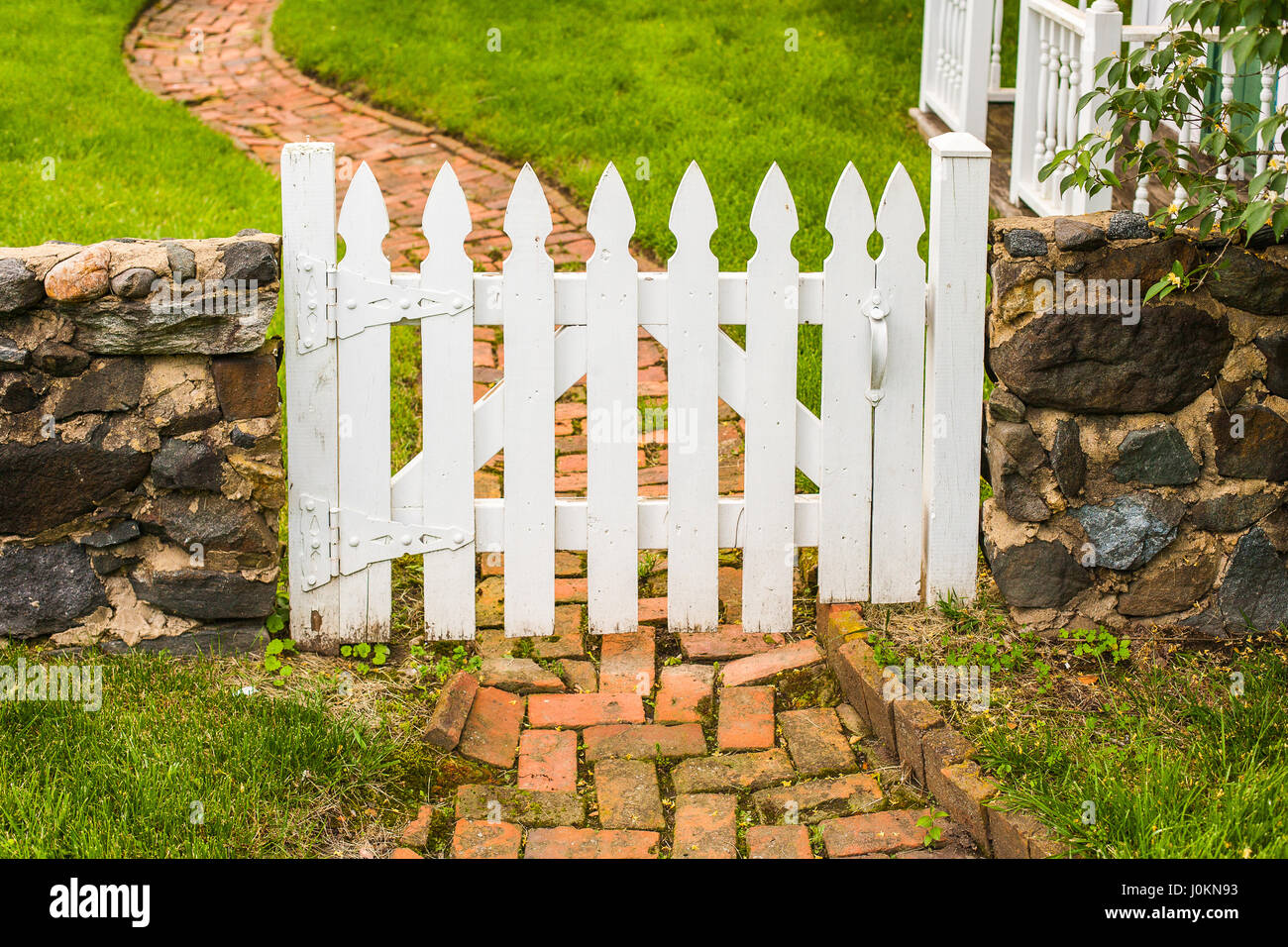 A White Wooden Picket Gate In A Low Stone Wall Across A