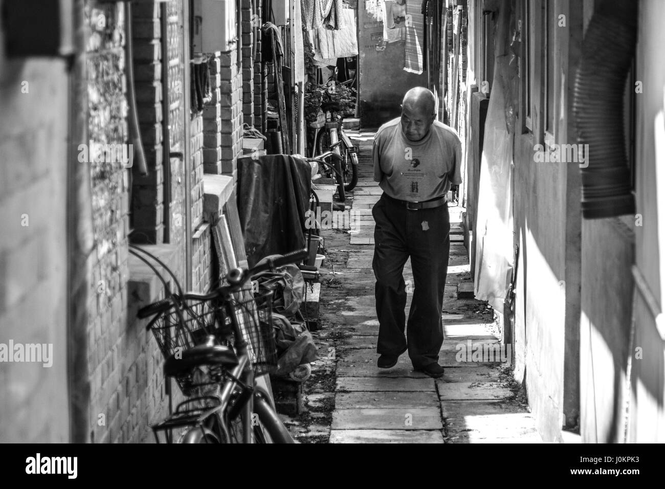 An elderly gentleman taking his morning stroll through the streets of Beijing - Stock Image