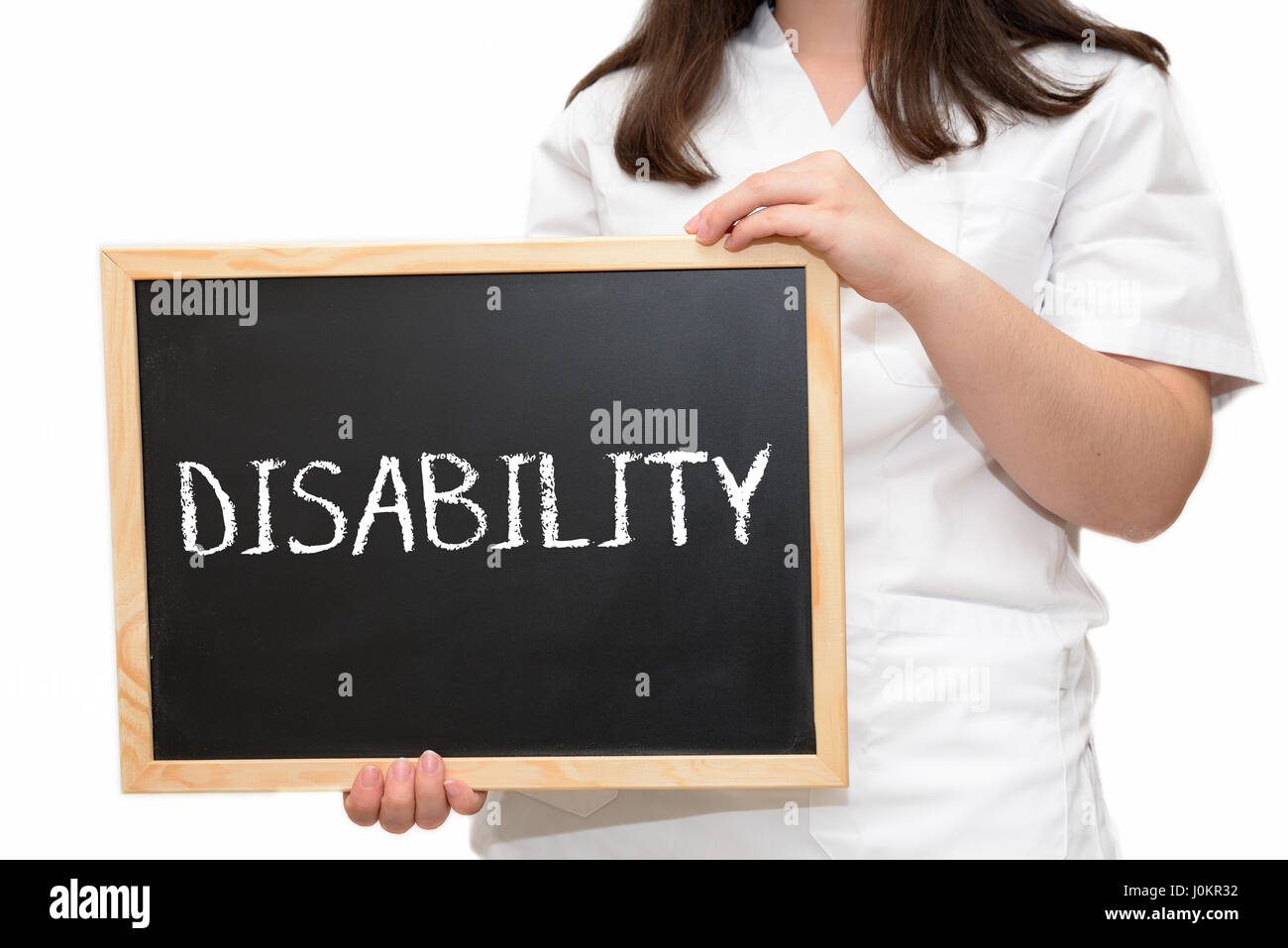 Female nurse holding a slate board with the text Disability written with chalk, isolated on white background. - Stock Image