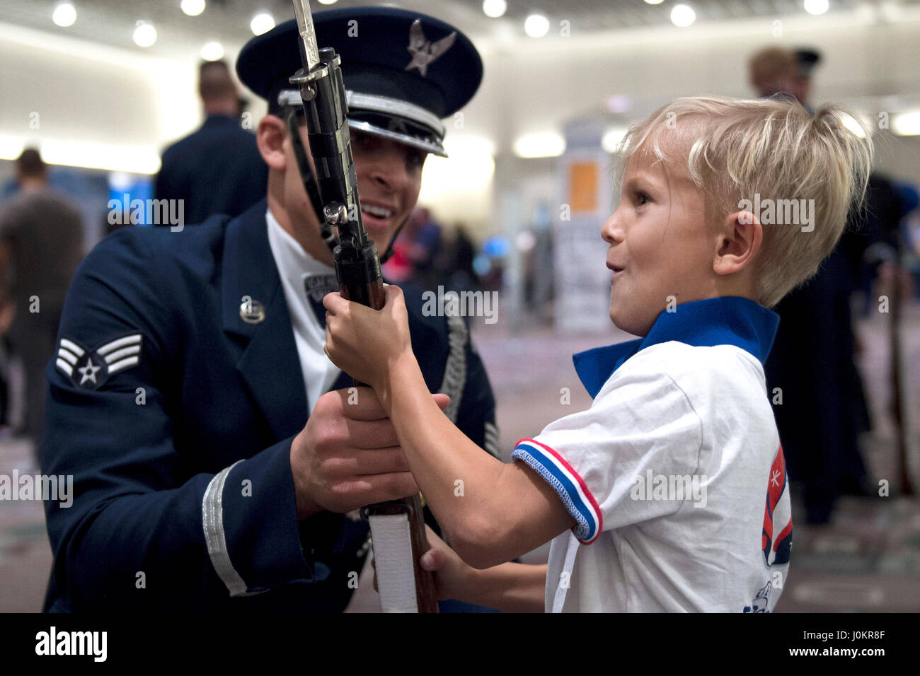 Senior Airman Angelo Hightower, an U.S. Air Force Honor Guard Drill Team member, lets a young boy hold a drill rifle - Stock Image