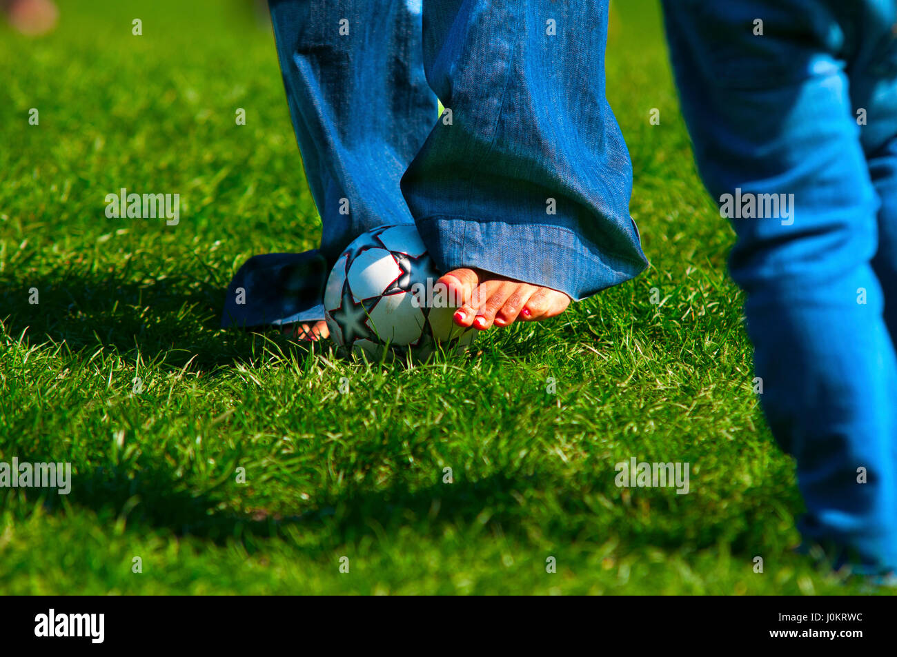 A person playing with a small soccer ball. - Stock Image