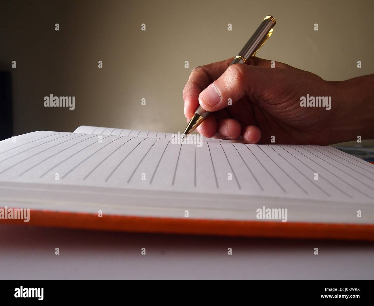 Hand with a pen writing on a page on a notebook. Stock Photo
