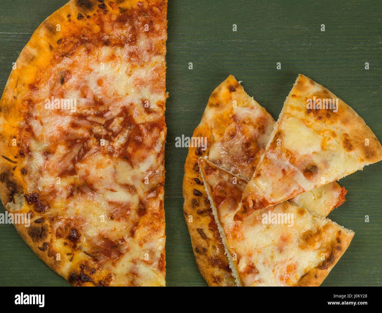 Cheese and Tomato Margherita Pizza Against a Green Background - Stock Image