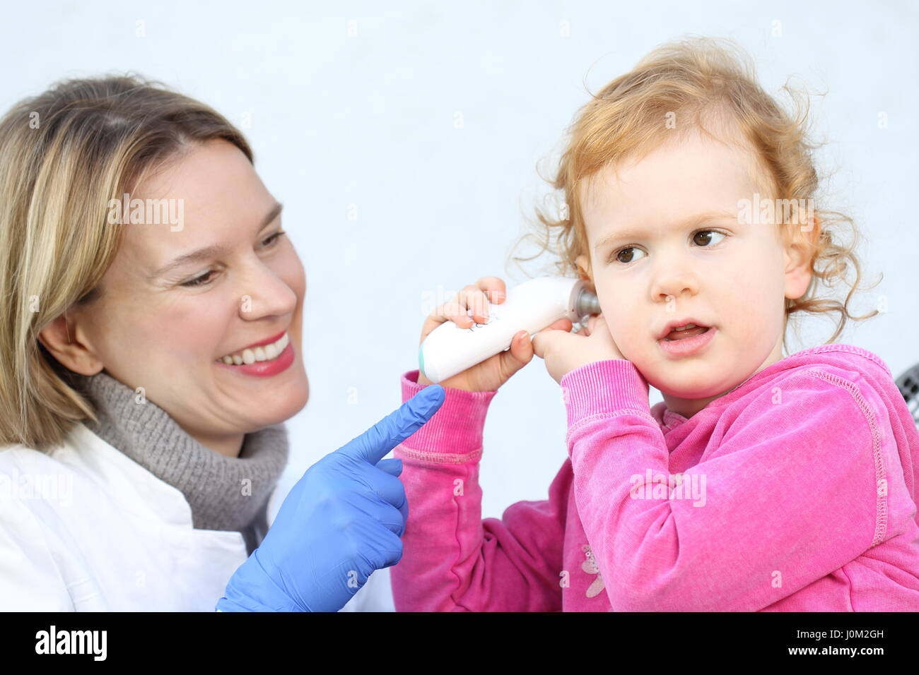 A Doctor measuring with InfraredThermomete temperature  a Child - Stock Image