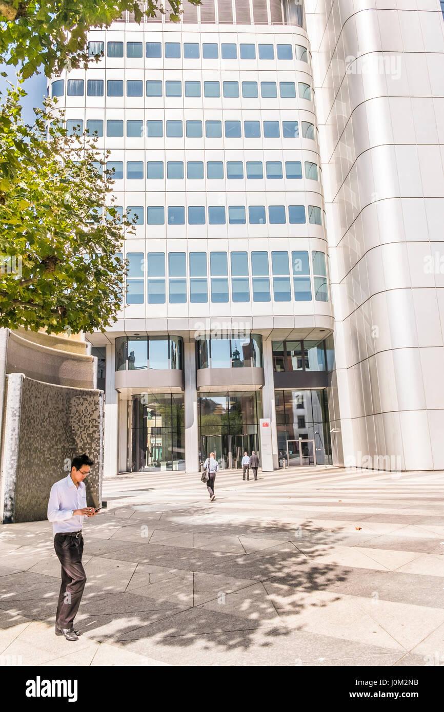 street scene in front  of silver tower, deutsche bahn office building - Stock Image